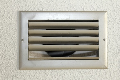 Small silver metal HVAC air vent with five slats in the white textured ceiling of an old home close up.